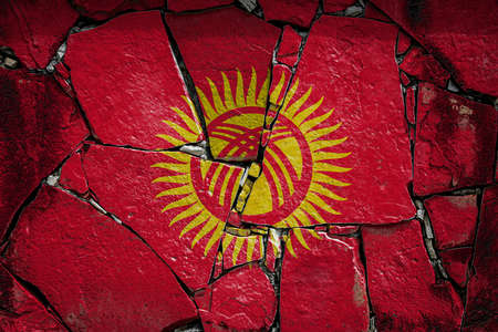 National flag of Kyrgyzstan depicting in paint colors on an old stone wall. Flag banner on broken wall background.