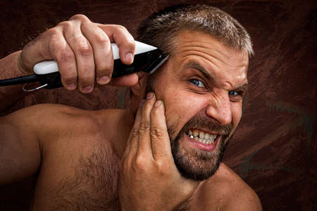 Close-up portrait of handsome shirtless man shaving his head with an electric razor and gritting his teeth, against brutal background. concept of male home care without beauty salons