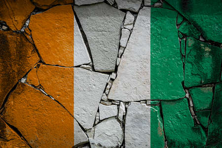 National flag of Cote d'ivoire depicting in paint colors on an old stone wall. Flag banner on broken wall background.