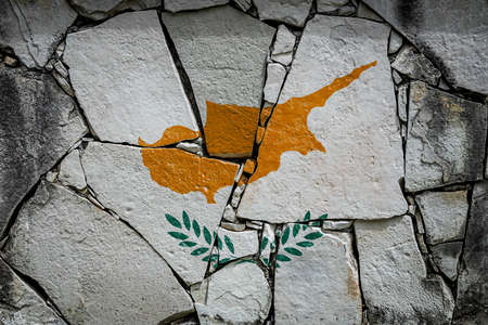 National flag of Cyprus depicting in paint colors on an old stone wall. Flag banner on broken wall background.