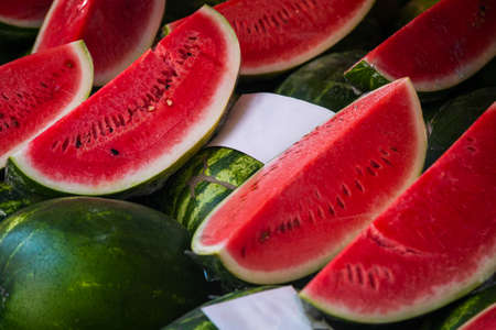 Close-up berry for background, fruit texture. Bright red watermelons sliced into wedges in a shop window