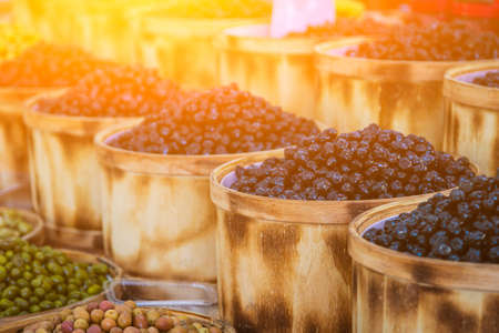 Sales of traditional products. Mediterranan olives in the market. Many bowls of black, brown and green olives at the farmer's market Archivio Fotografico