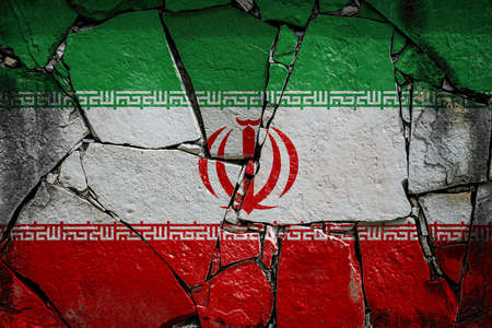 National flag of Iran depicting in paint colors on an old stone wall. Flag banner on broken wall background.