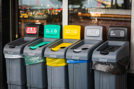 There are five trash cans on the street: red for masks, green for glass, yellow for plastic and packaging, gray for metal, and black for residual waste. Garbage sorting concept.