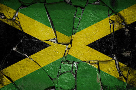 National flag of Jamaica depicting in paint colors on an old stone wall. Flag banner on broken wall background. Stock fotó
