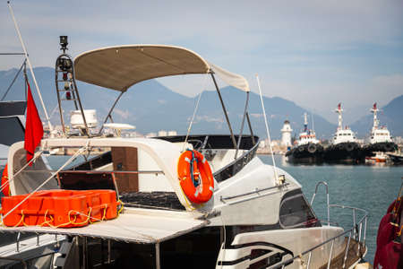 Wooden side of the boat, painted white and brown, with a orange lifebuoys and ropes against the background of sea water