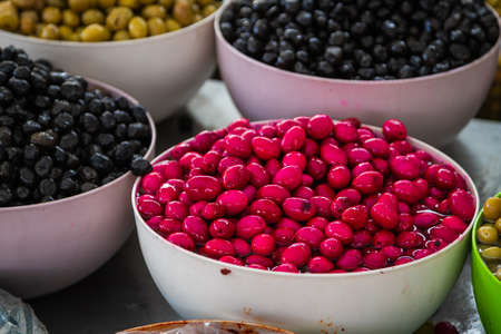 Sales of traditional products. Mediterranan olives in the market. Many bowls of black, pink and green olives at the farmer's market Stock fotó