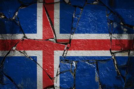 National flag of Iceland depicting in paint colors on an old stone wall. Flag banner on broken wall background.