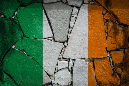 National flag of Ireland depicting in paint colors on an old stone wall. Flag banner on broken wall background. Stock fotó