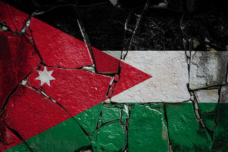 National flag of Jordan depicting in paint colors on an old stone wall. Flag banner on broken wall background. Stock fotó