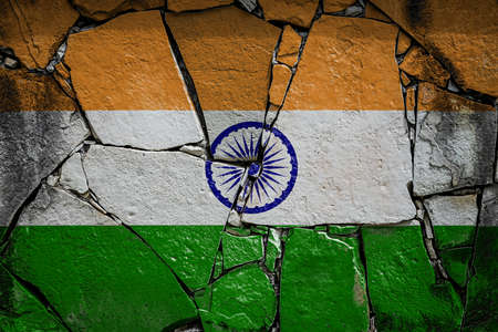 National flag of India depicting in paint colors on an old stone wall. Flag banner on broken wall background.
