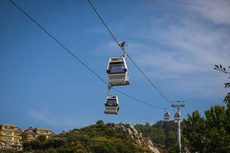 Rope way over cloudy blue sky. Funicular cabins and aerial city skyline panoramic view in Turkey