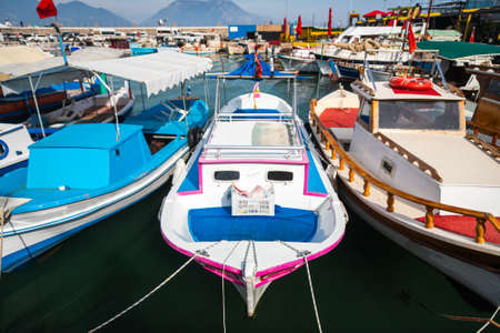 Wooden boards of boats, painted white and brown, moored to the pier with ropes against the background of sea water. Stock fotó