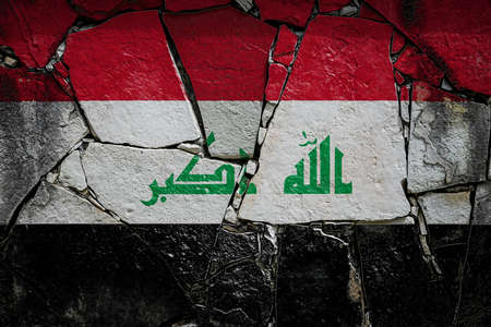 National flag of Irak depicting in paint colors on an old stone wall. Flag banner on broken wall background.