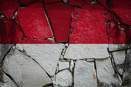 National flag of Indonesia depicting in paint colors on an old stone wall. Flag banner on broken wall background.