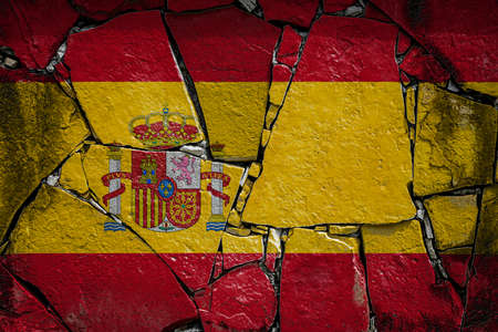 National flag of Spain depicting in paint colors on an old stone wall. Flag banner on broken wall background. Stock fotó