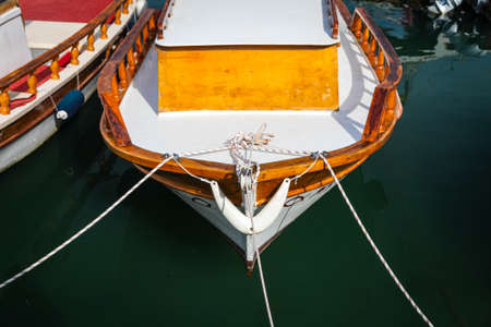 Wooden side of the boat, painted white and brown, with a beautiful wooden fence and ropes against the background of sea water Stock fotó
