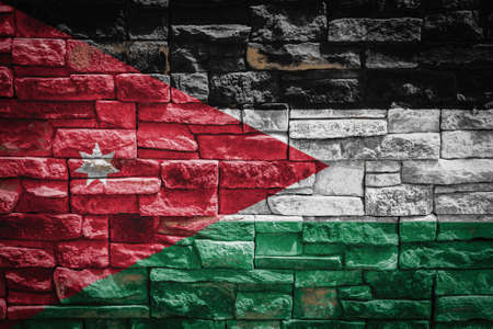 National flag of Jordan on stone wall background. The concept of national pride and symbol of the country. Flag banner on stone texture background.