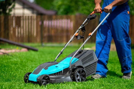 Close-up of a man in overalls with a lawn mower cutting green grass in a modern garden. Lawn mowing machine. Фото со стока