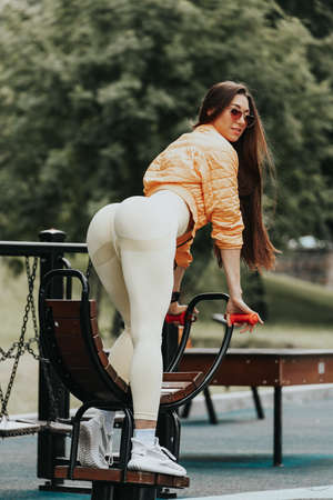 Fitness sportive woman showing her well trained body and flat belly, smiling cute while posing for camera on city background