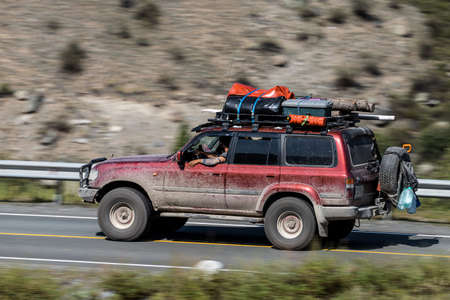 Novosibirsk, Russia - August 08, 2021: red Toyota Land Cruiser jeep driving fast on freeway in highlands on summer day on background forest
