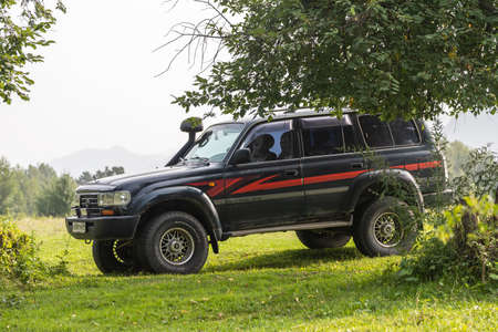 Novosibirsk, Russia - August 08, 2021: black Toyota Land Cruiser jeep is parked on a green meadow near the forest. Traveling by car in the highlands