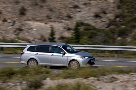 Novosibirsk, Russia - August 08, 2021: silver Toyota Fielder driving fast on freeway in highlands on summer day on background forest
