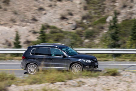 Novosibirsk, Russia - August 08, 2021: black Volkswagen Tiguan driving fast on freeway in highlands on summer day on background forest