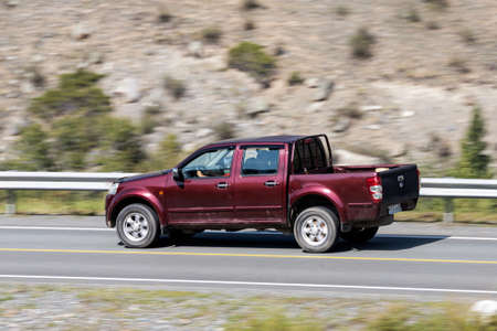 Novosibirsk, Russia - August 08, 2021: red Toyota Hilux pickup driving fast on freeway in highlands on summer day on background forest
