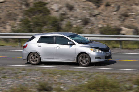 Novosibirsk, Russia - August 08, 2021: silver Toyota Matrix driving fast on freeway in highlands on summer day on background forest
