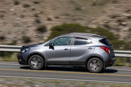 Novosibirsk, Russia - August 08, 2021: silver Opel Mokka driving fast on freeway in highlands on summer day on background forest