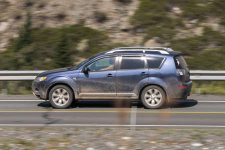 Novosibirsk, Russia - August 08, 2021: blue Mitsubishi Outlander driving fast on freeway in highlands on summer day on background forest