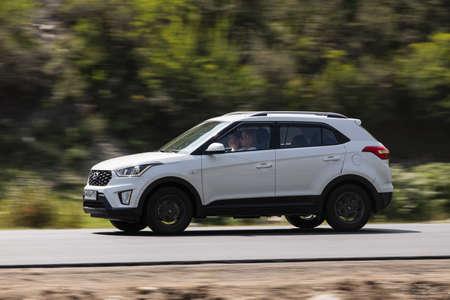 Novosibirsk, Russia - August 08, 2021: Hyundai Creta driving fast on freeway in highlands on summer day on background forest