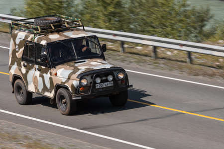 Novosibirsk, Russia - August 08, 2021: UAZ Patriot driving fast on freeway in highlands on summer day on background forest