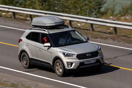 Novosibirsk, Russia - August 08, 2021: silver Hyundai Creta driving fast on freeway in highlands on summer day on background forest