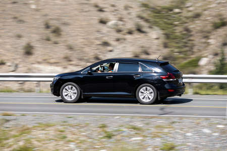 Novosibirsk, Russia - August 08, 2021: black Toyota Venza driving fast on freeway in highlands on summer day on background forest 新聞圖片