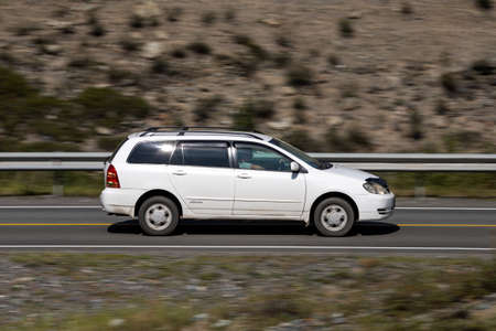 Novosibirsk, Russia - August 08, 2021: white Toyota Fielder driving fast on freeway in highlands on summer day on background forest