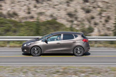 Novosibirsk, Russia - August 08, 2021: brown Kia Ceed driving fast on freeway in highlands on summer day on background forest