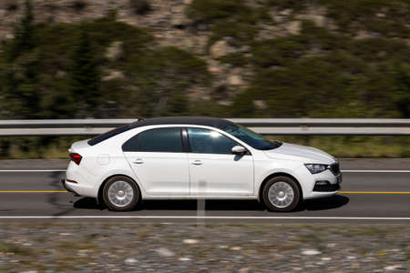 Novosibirsk, Russia - August 08, 2021: white Scoda Octavia driving fast on freeway in highlands on summer day on background forest