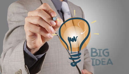businessman hand with a pen drawing light bulb Stock Photo - 16707135