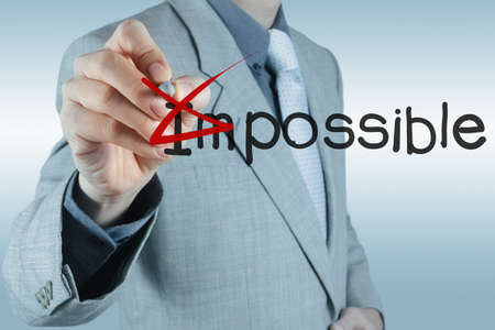 Businessman hand changing the word impossible into possible photo