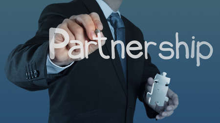 complete solution: businessman hand shows light and puzzle partnership Stock Photo