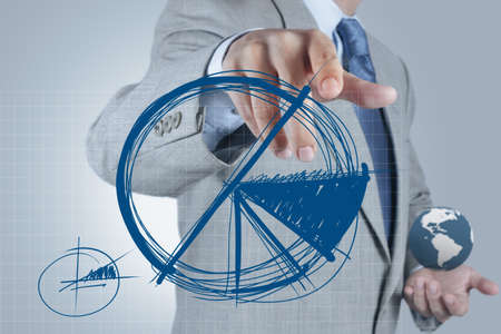 businessman hand drawing a pie chart and 3d graph Stock Photo - 16704298