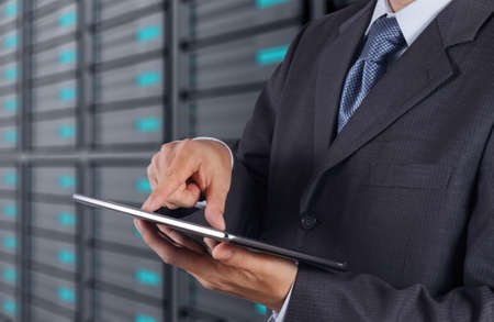 businessman hand using tablet computer and server room background photo