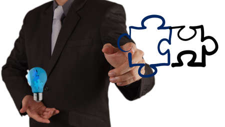 businessman hand shows light and puzzle partnership Stock Photo - 16703555