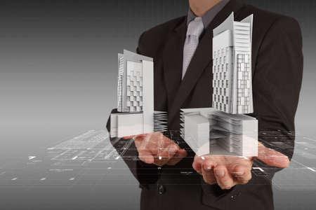 real estate growth: businessman draws building development concept