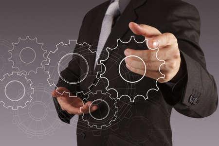 mechanical men: businessman hand show gear to success as concept