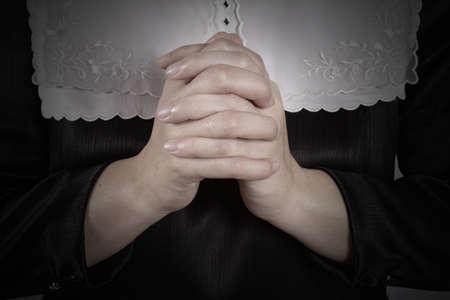black nun: hand of nun praying on black background