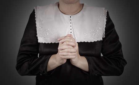 devotions: hand of nun praying on black background