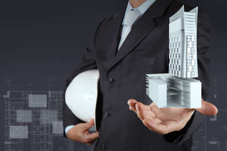 businessman hand presents building development as concept photo